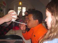 Zum Abschluss wird ein Ei fuer das Straussenruehrei von den Kindern ausgeblasen